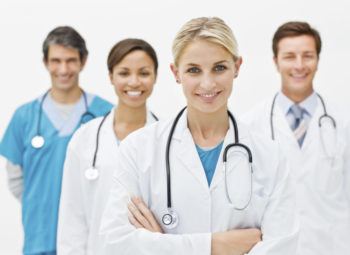 Young doctor standing in front with 3 doctors behind her